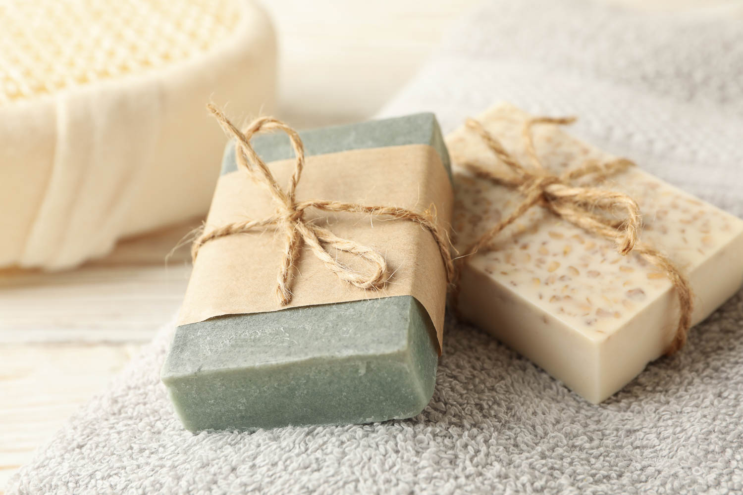 Towel and natural soap on wooden background